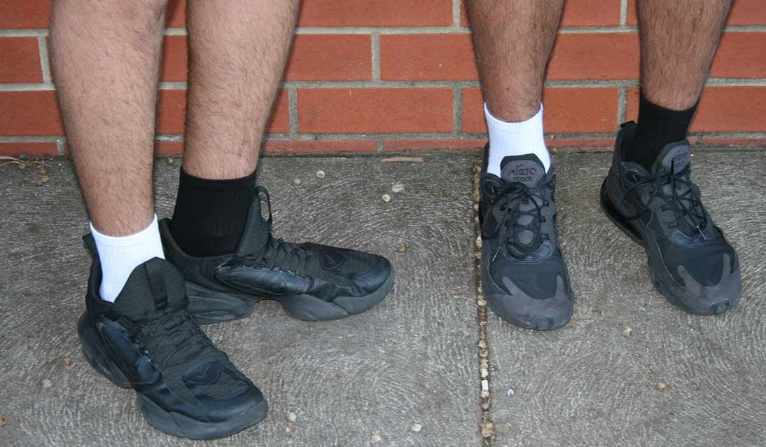 Two sets of feet in shoes both with one black sock and one white sock.