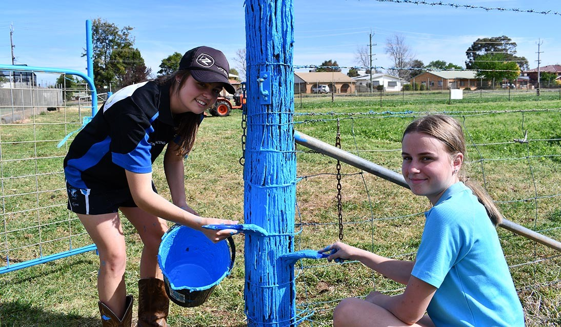 Two students painting a fence post blue.