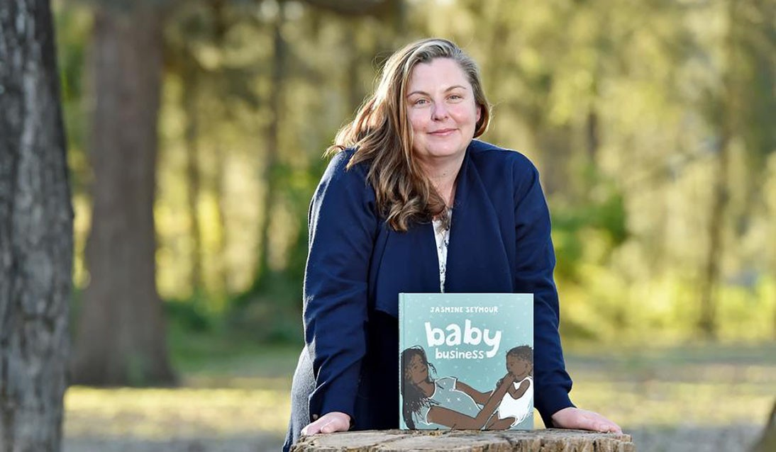 Woman wearing navy blue jacket leans against a tree stump outside with picture book Baby Business resting on top of the tree stump. Trees are in the background.