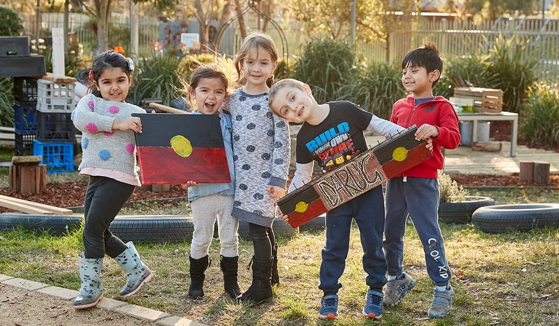 A group of preschool students holding painted Aboriginal flags and a sign with the word Darug.