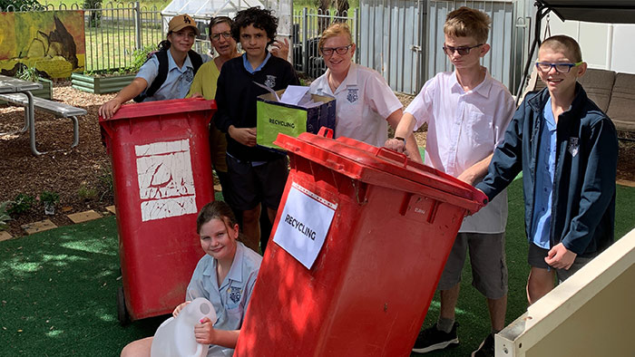 A group of students and one teacher standing near red recycling bins.