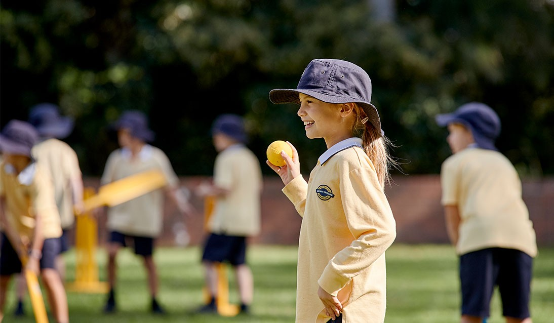 A primary school girl bowls a cricket ball while other students play with bats in the background.
