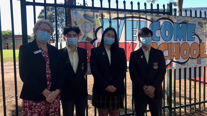 Group of senior students and teacher outside school gate