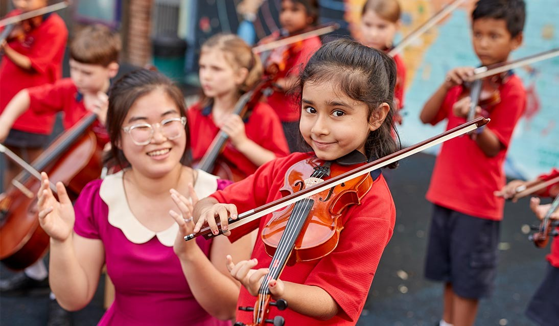 A young girl plays the violin while her teacher watches.