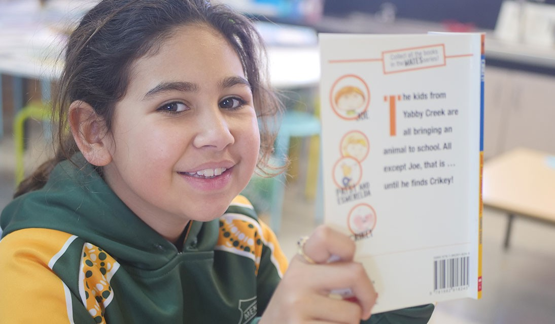 An Aboriginal schoolgirl reads a novel.