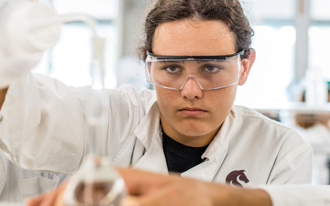 Aboriginal student in white lab coat pours liquid into a beaker