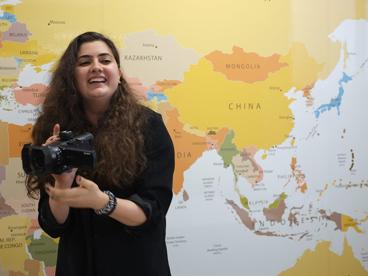 Joelle holding a camera, standing in front of a world map