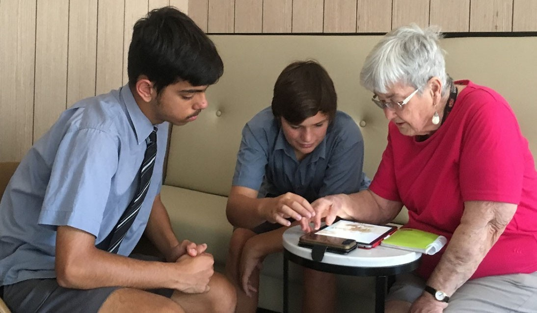 Two young boys sit with an elderly woman showing her how to use an iPad