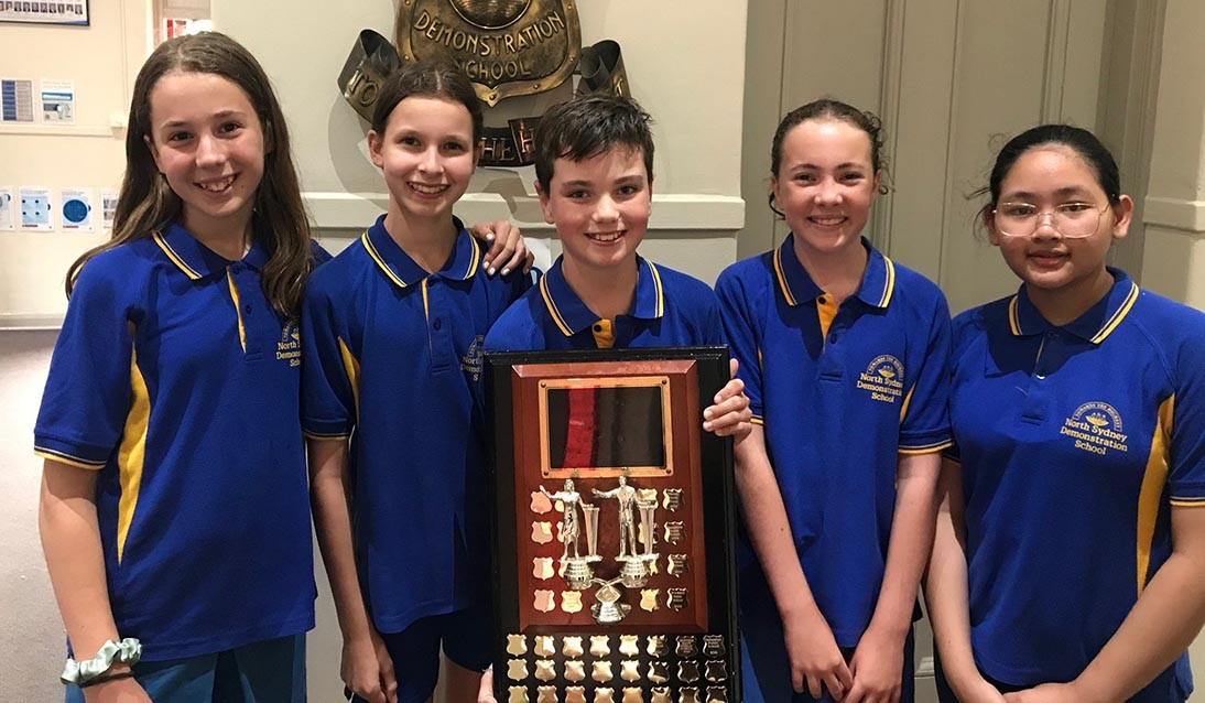 Five students wear blue uniform and hold a trophy.