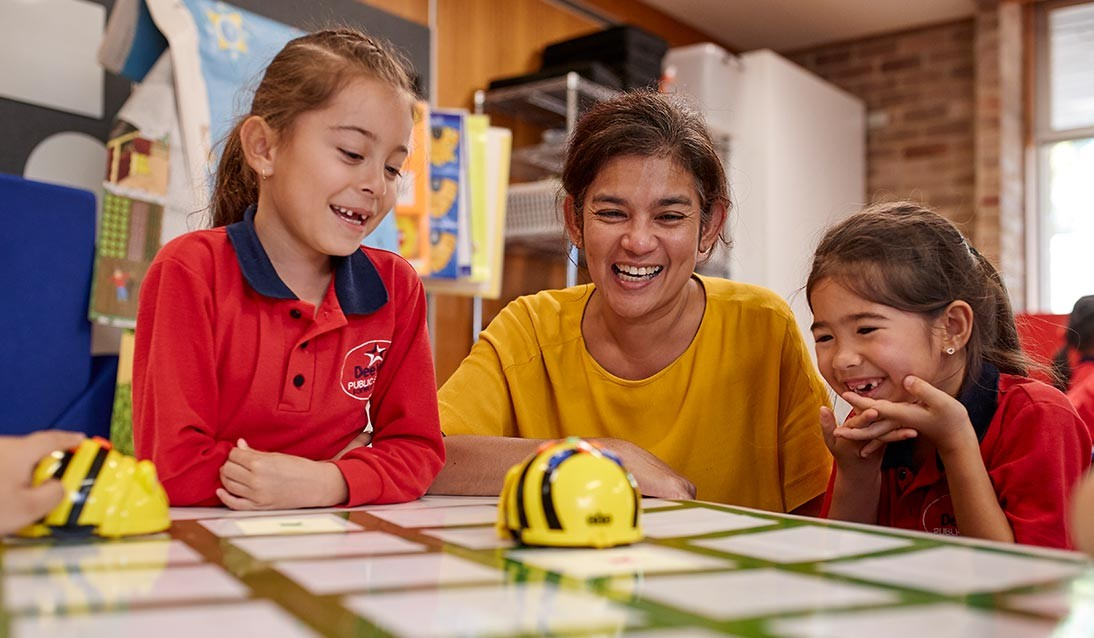 Two primary school girls and a teacher play with beebots in the classroom.