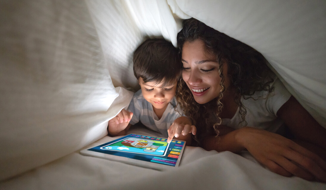 A mother and young child play on a tablet inside a pillow fort.