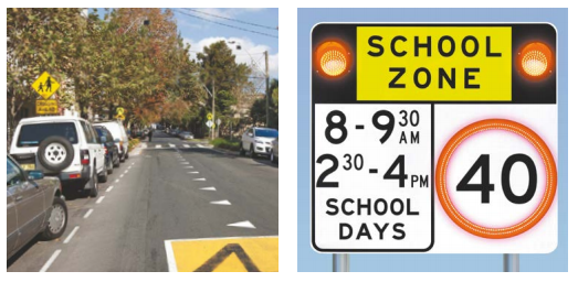 A school zone sign and a road outside a school.