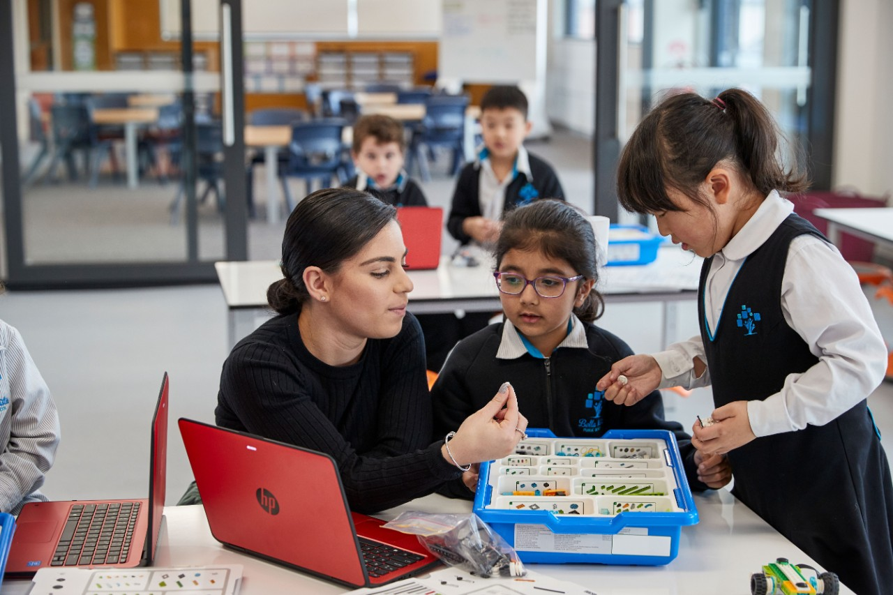 A primary school teacher works with two students in a classroom with a laptop on the desk.