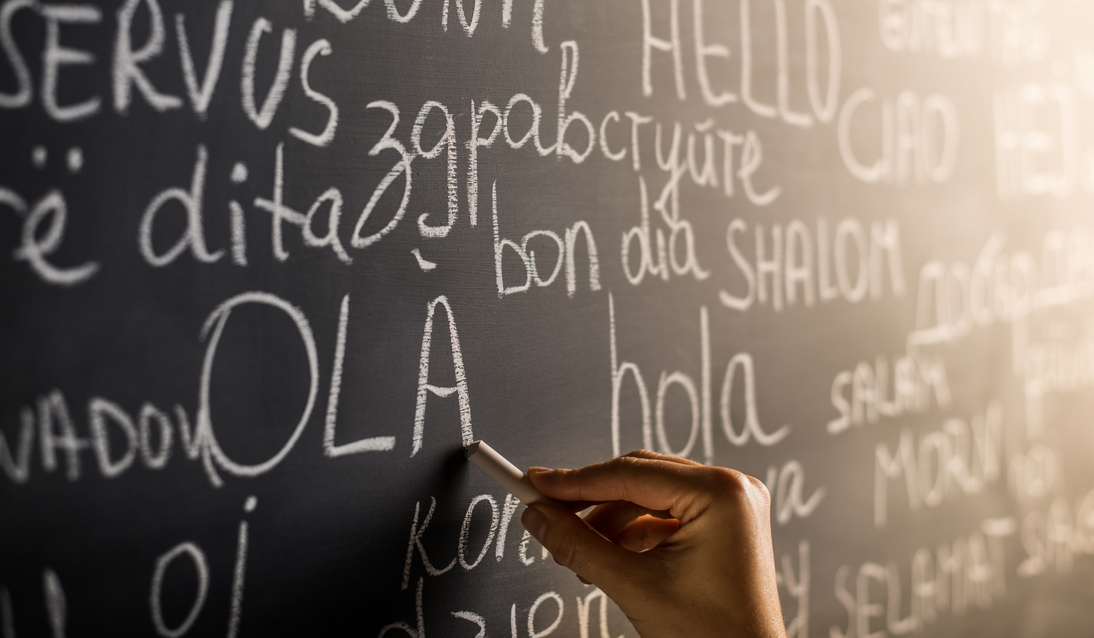 "A hand writing ""hello"" in various languages on a blackboard"