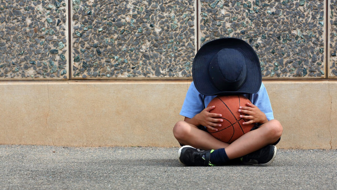 Child sitting on the ground, holding a basketball, with their face hidden by a hat