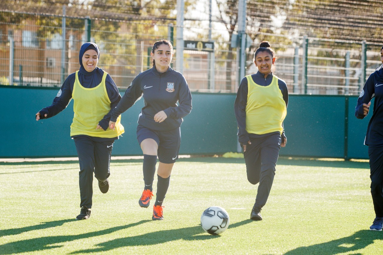 Three girls playing soccer