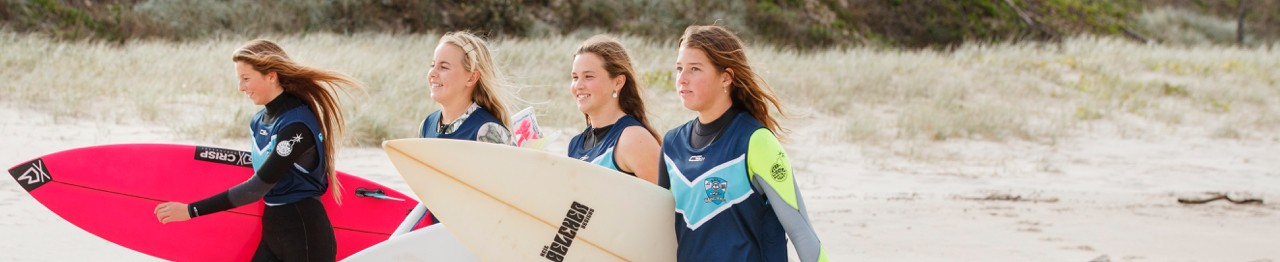 High school students on beach walking with surfboards