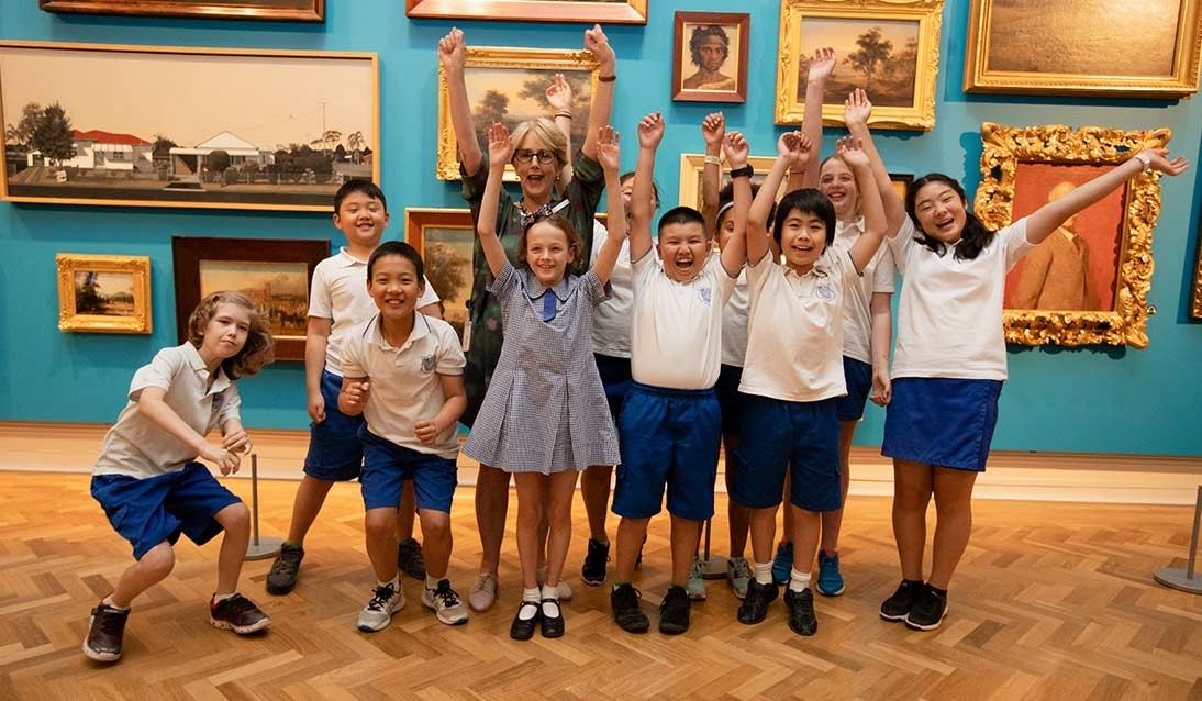A group of primary-aged students and an adult raise their arms in excitement in front of a collection of artworks on a wall