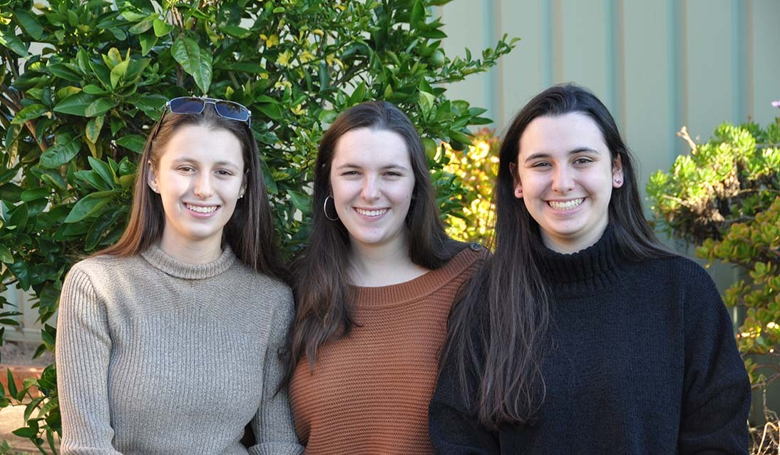 Three females with brown hair stand next to each other, outside in front of a green tree.