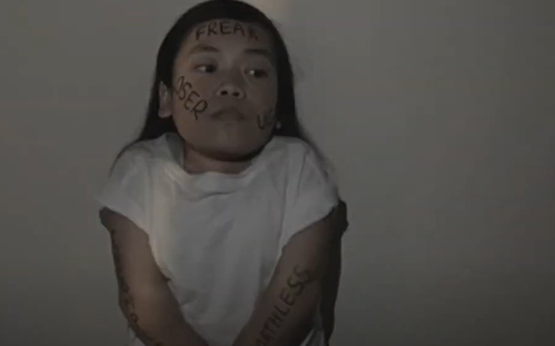A young woman with cruel words written on her face and limbs