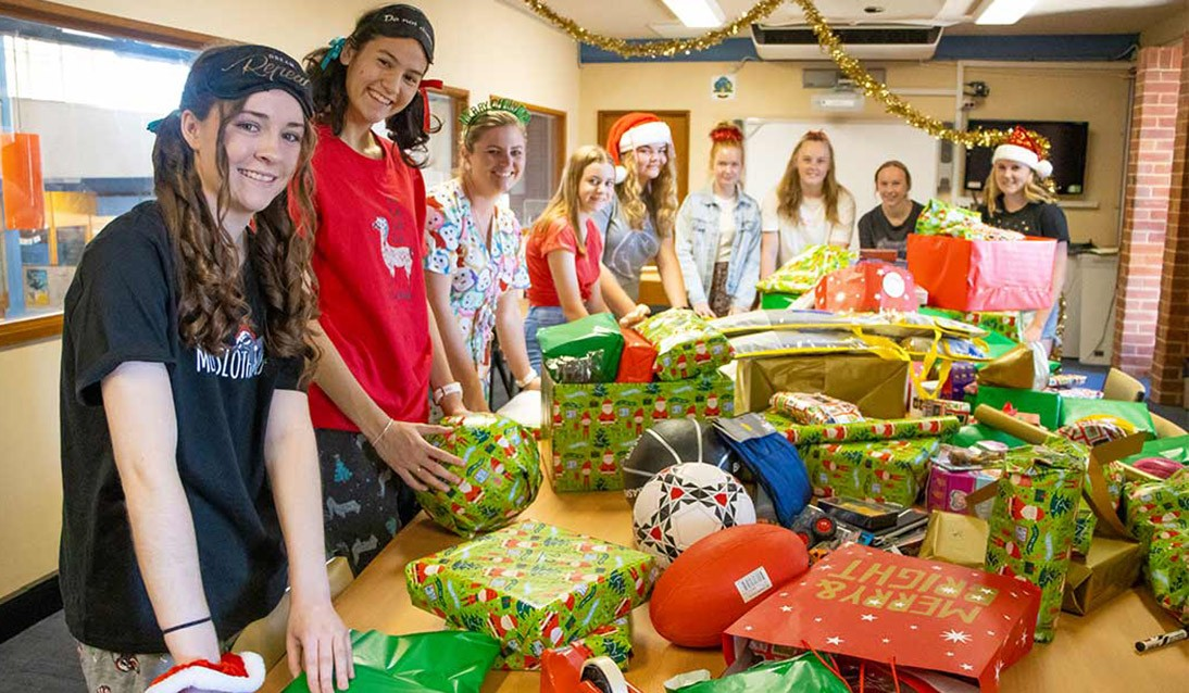 Students stand around wrapped Christmas presents sitting on a table.