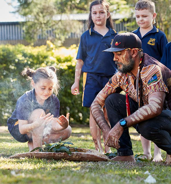 A young girl takes part in a smoking ceremony conducted by a young Aboriginal man.