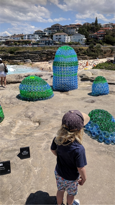 Plastic sculpture by Kathy Allam, on the seaside clifs during the 2017 Sculpture by the sea exhibition. Shapes made from blue and green plastic bottles.
