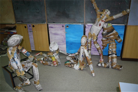 Paper people sculptures in the classroom. 5 sculptures showing people forms in various positions some seated some standing..