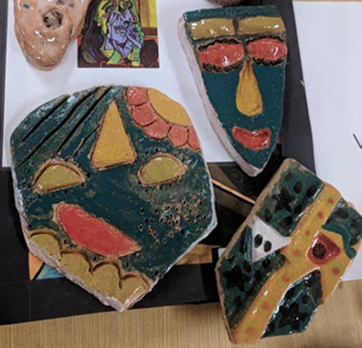 Examples of students ceramic masks green masks with yellow, red and orange features.