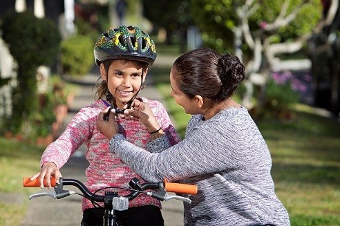 Adult woman checking the helmet of a girl seated on a bicycle