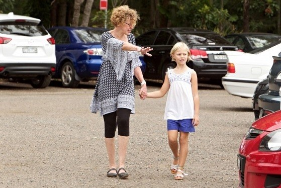 Woman holding girls hand in a carpark gesturing at cars