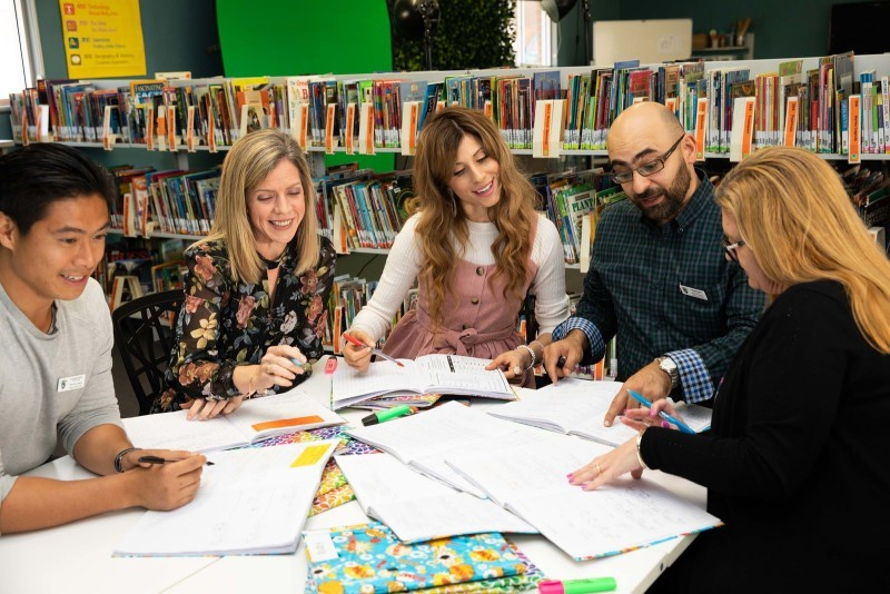 A group of five teachers comprising beginning teachers and their supervisors or in school mentors are engaged in a round table discussion together in the school library  They have a number of samples of students work open in front of them which they are reviewing and analysing.