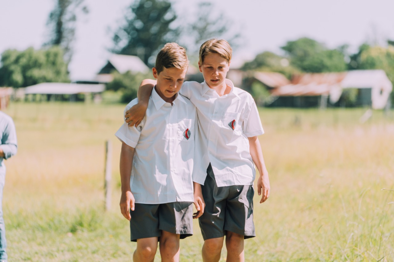Two male primary students standing side by side in a field with one arm over the others shoulders