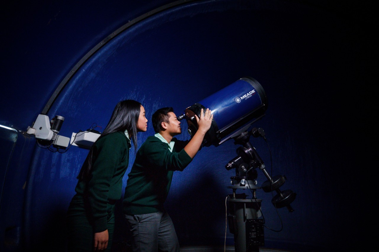 High school student looking through telescope with other student watching
