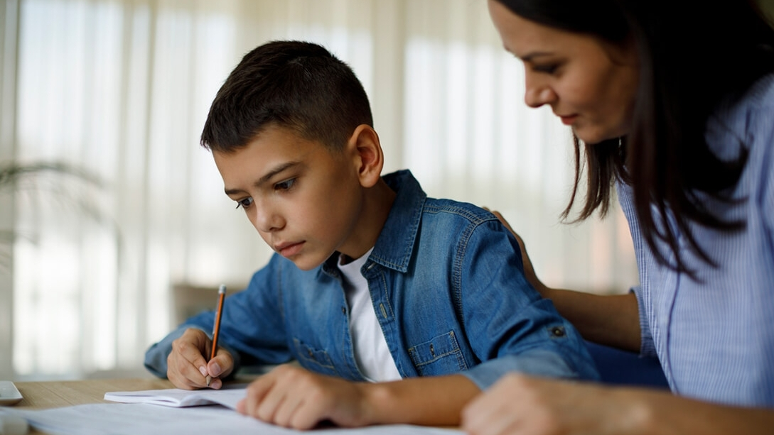 Child doing homework with his mother