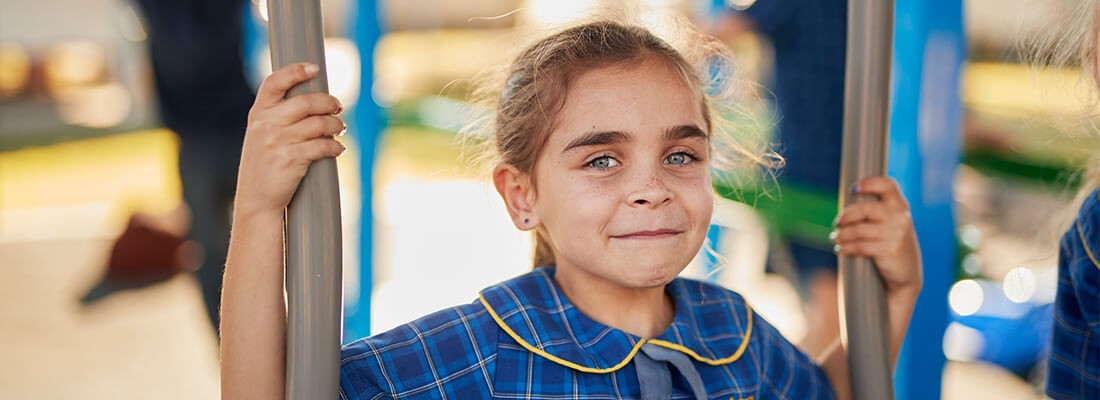 Young girl in school uniform in school playground smiles at the camera