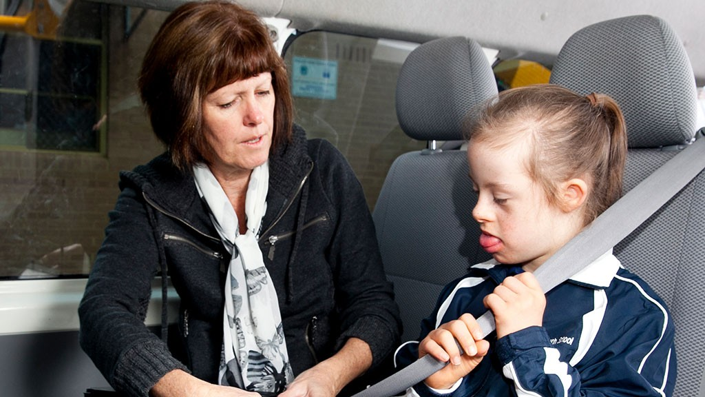 Female support officer helping young a female student with a disability fasten her seatbelt.