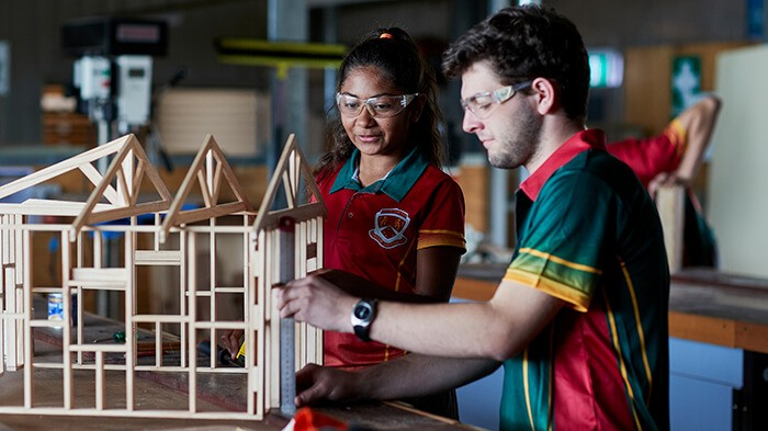 Two students work on a model of a building