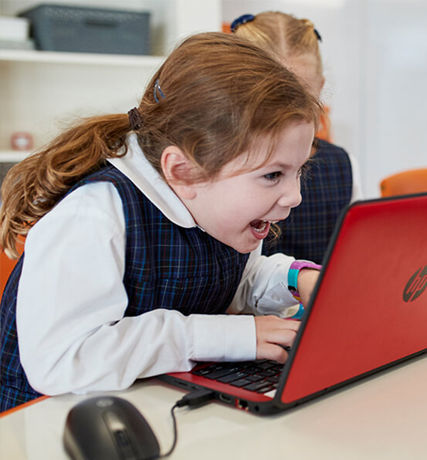 A child looks excitedly at her laptop screen