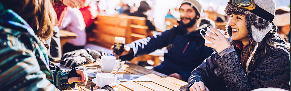 People in skiing or snowboarding gear drinking coffee outdoors at the snow