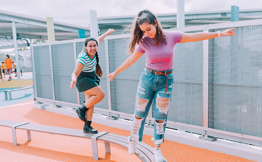 Two teenagers balancing on a school bench