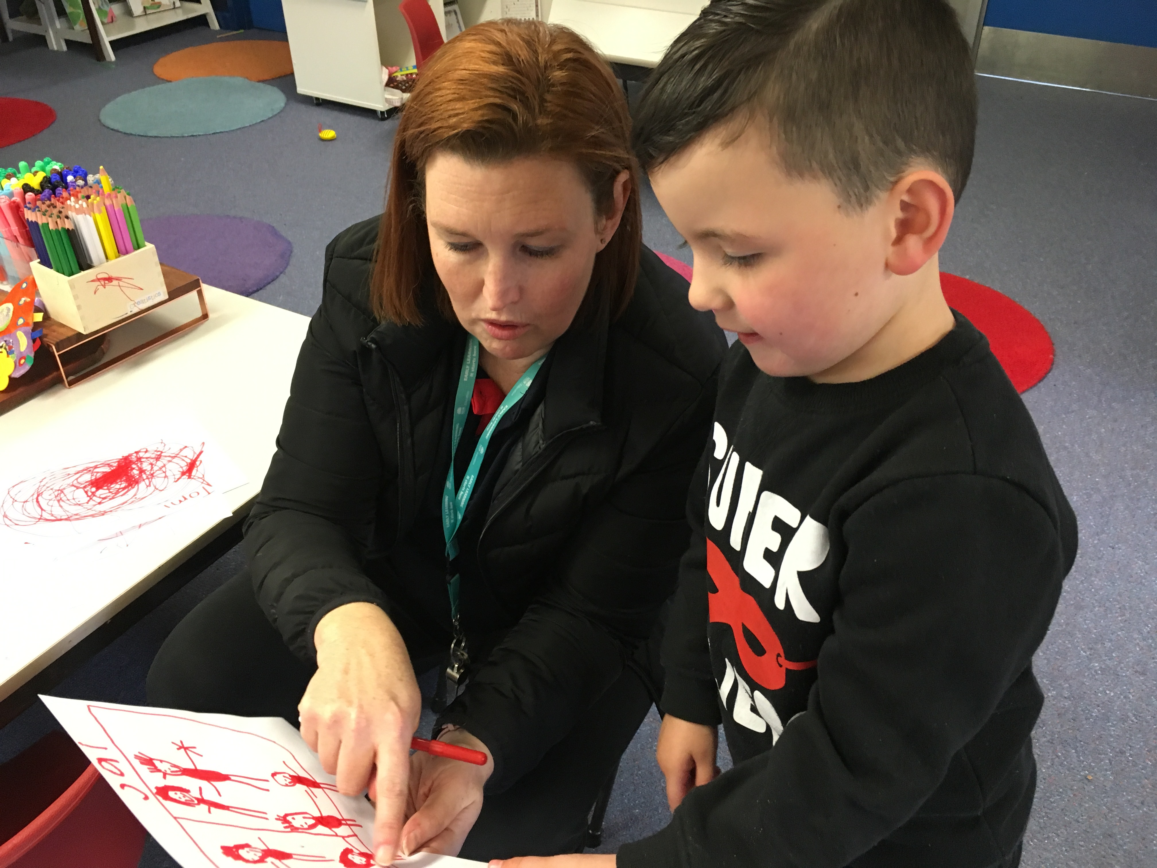 Young boy with his teacher reading an illustrated book