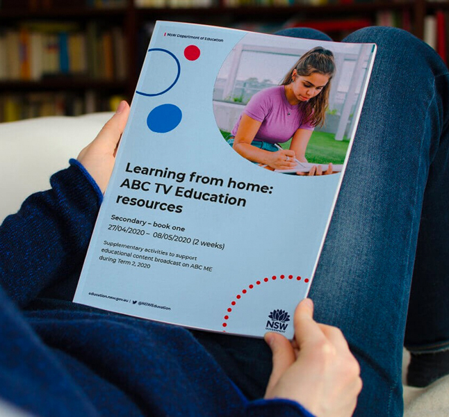 "Person holding a printed booklet with the title ""Learning from home: ABC TV Education resources""."