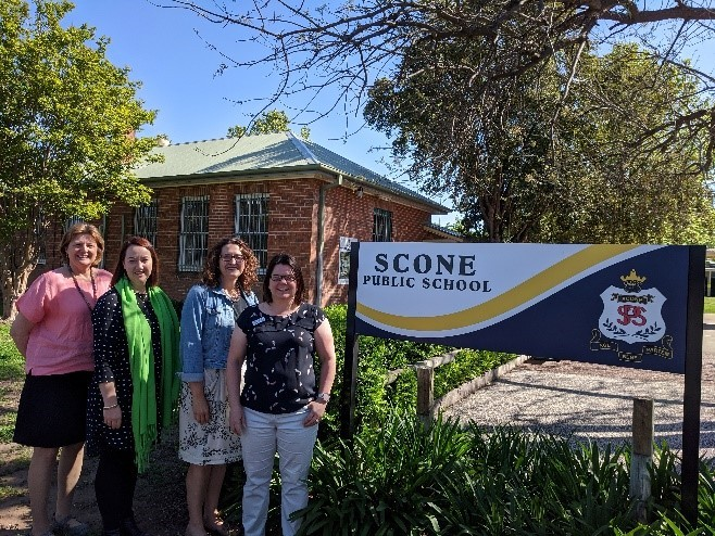 Staff posing outside Scone Public School next to school sign