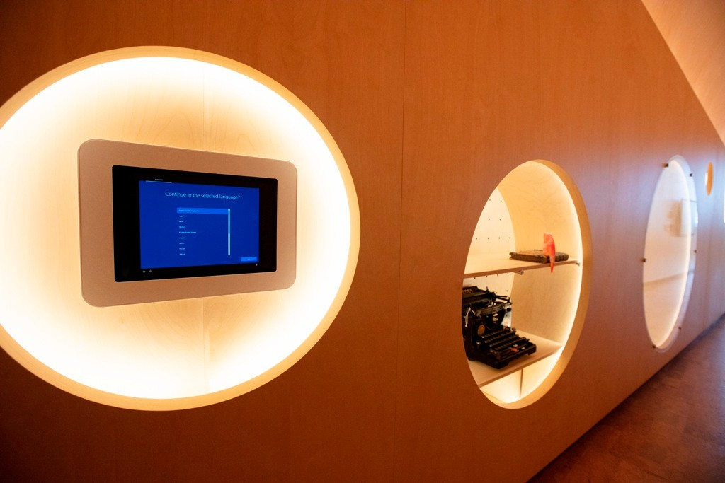 Timber clad wall with circular cut outs for small museum style displays and a touch screen
