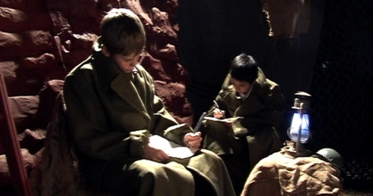 Students, dressed as soldiers, write letters by lamp light