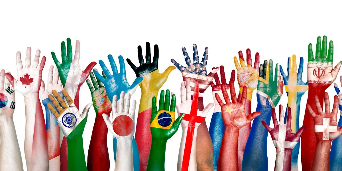 A group of raised hands, each painted with different flags